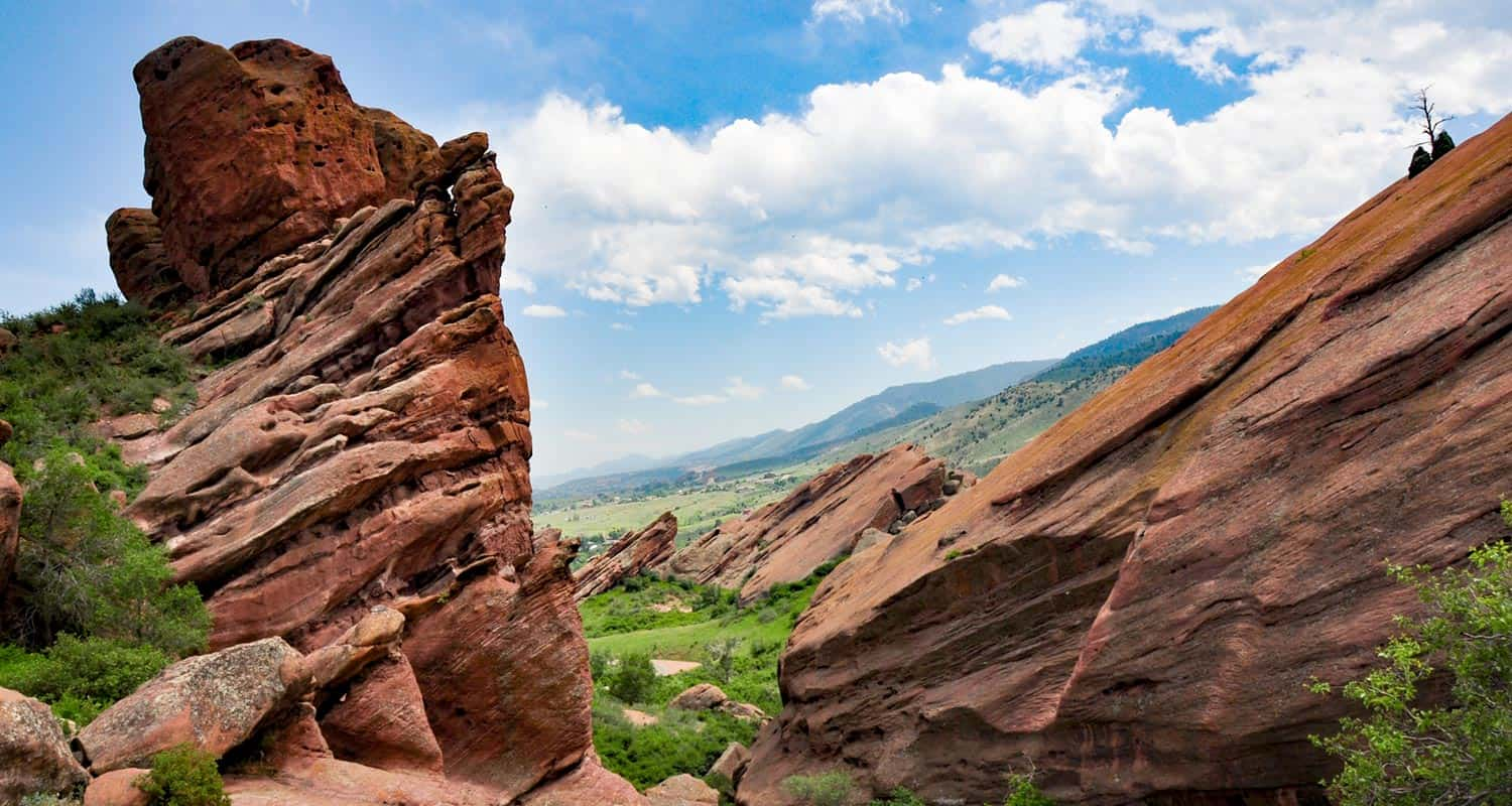 red rocks with blue sky background and green trees along trading post trail red rocks park in Denver Colorado