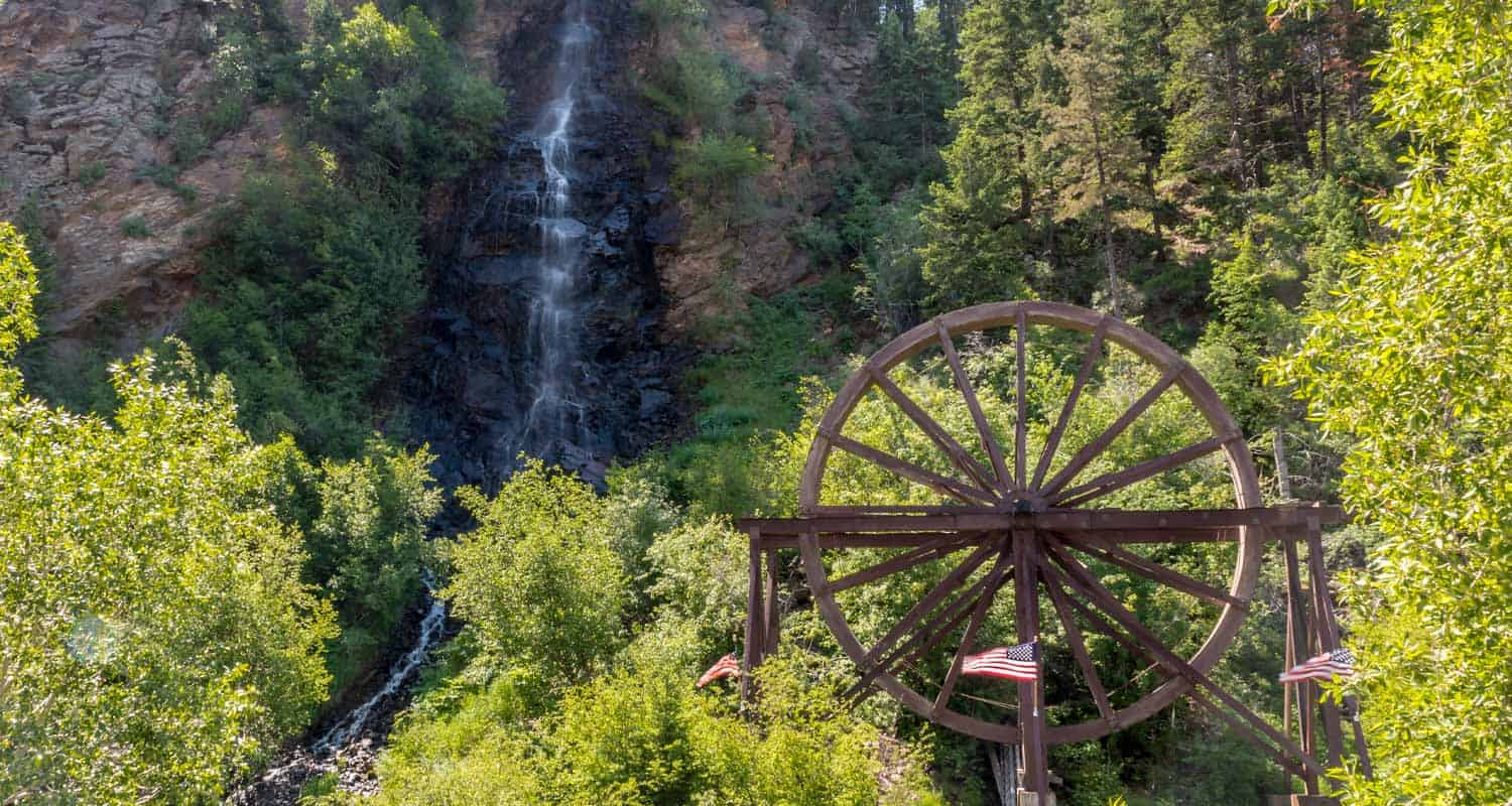 bridal veil falls waterfall pouring over cliff face with waterwheel at base among green trees in idaho springs colorado