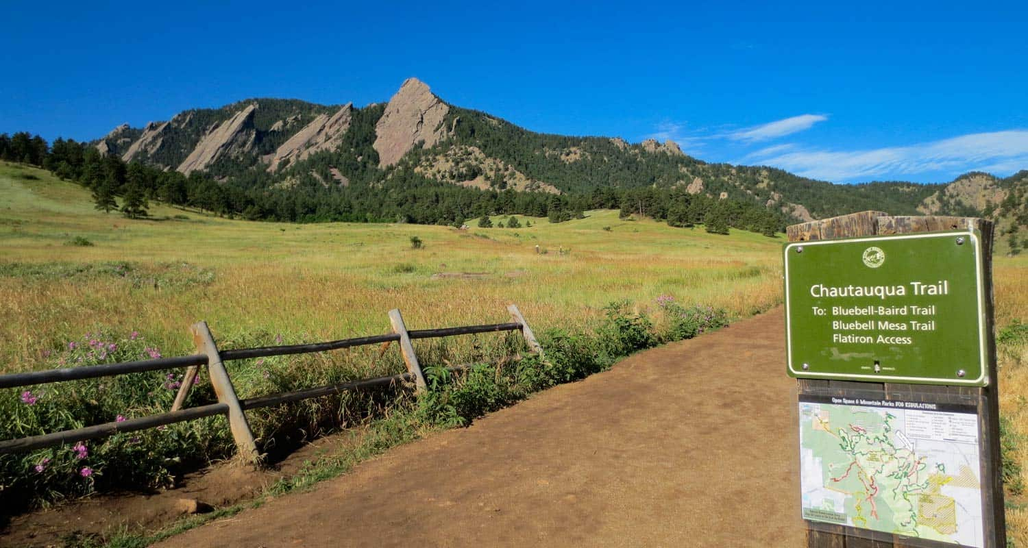 dirt trail leading toward the flatirons of boulder colorado in chautauqua park wooden fence in foreground and broad meadows