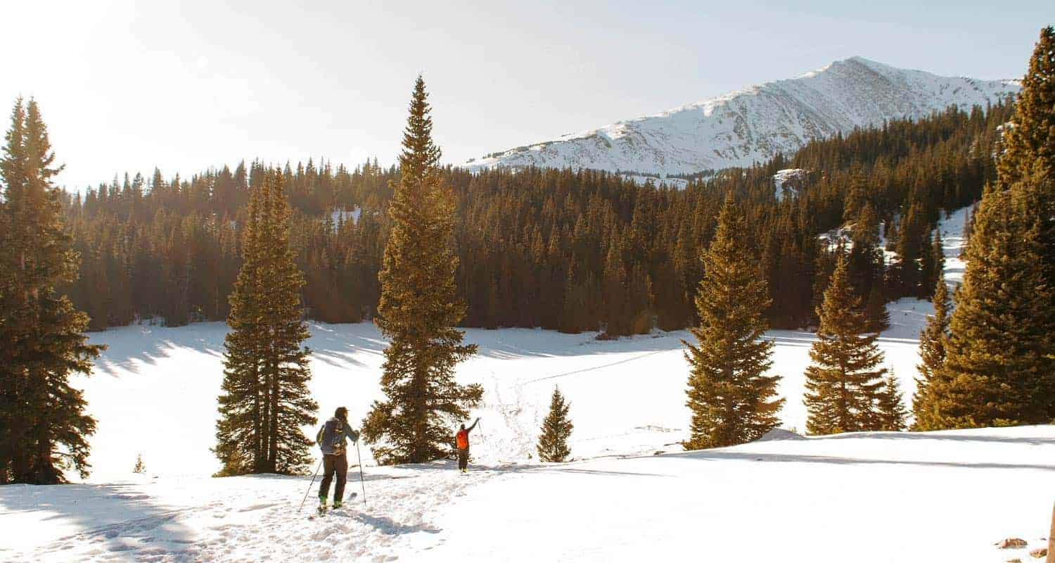 hikers in snow covered landscape with distant landscape winter hikes near denver