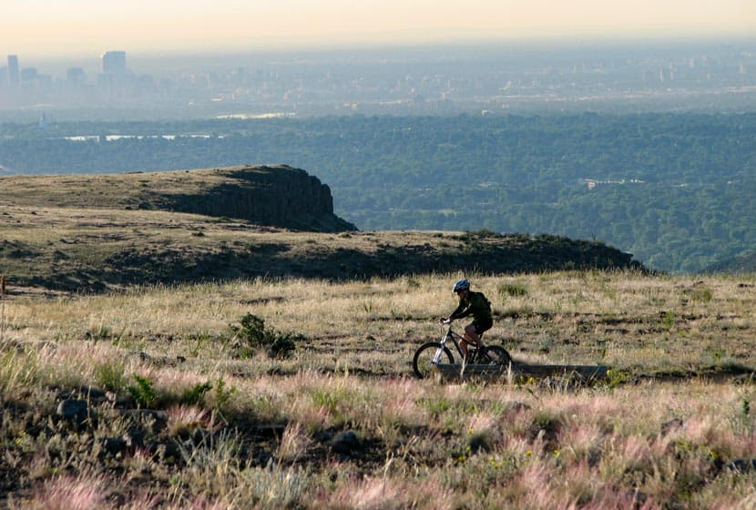 mountain biker on top of north table mountain with denver skyline in background