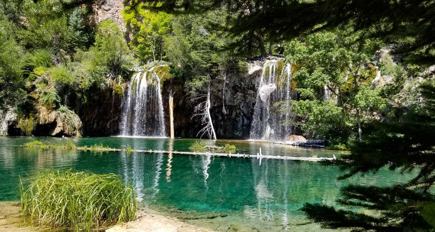 hanging lake waterfall flowing over verdant cliff face into turquoise pool on hike near glenwood springs colorao