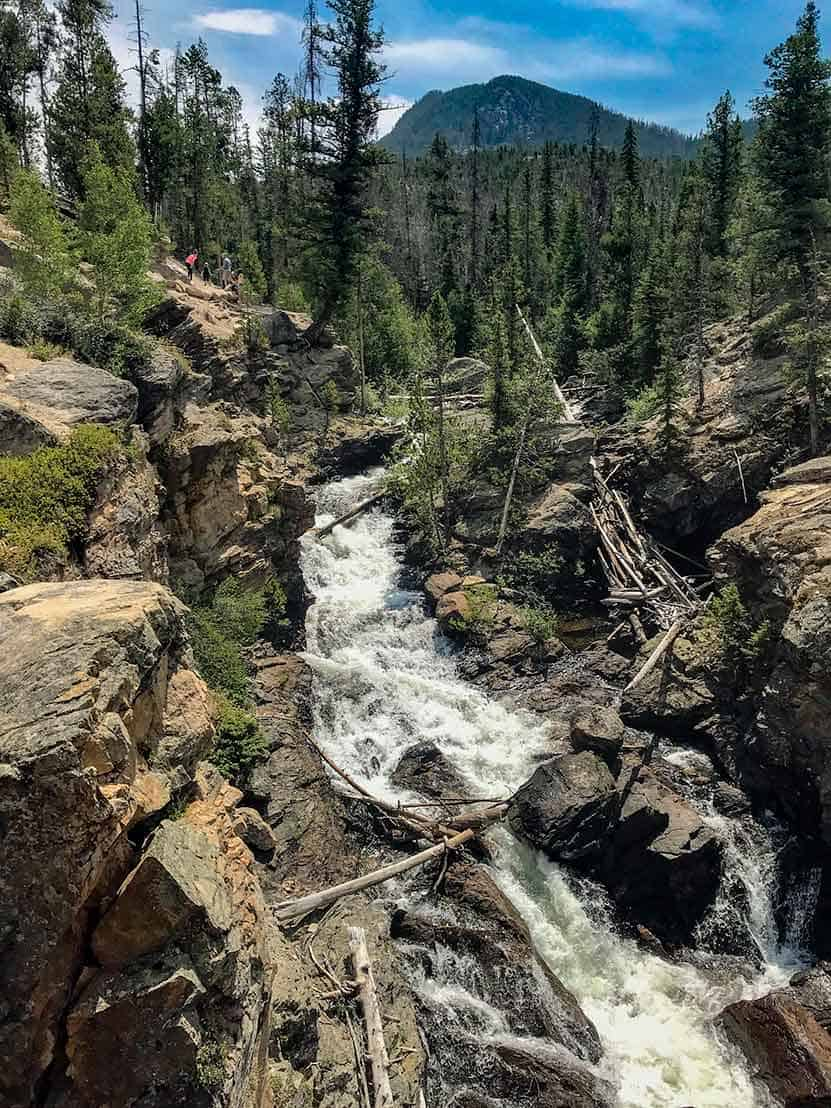 waterfall tumbling over rock with mountain and trees in background rocky mountain national park adams falls
