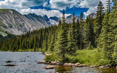 long lake in indian peaks wilderness colorado clouds and blue sky with jagged moutnains, evergreen trees and lake
