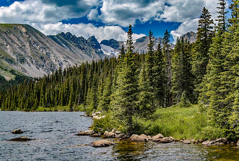 long lake in indian peaks wilderness colorado clouds and blue sky with jagged mountains, evergreen trees and lake