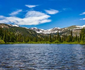 mountain lake with snowcapped mountains and evergreen trees in foreground with blue sky and cirrus clouds lost lake near nederland colorado