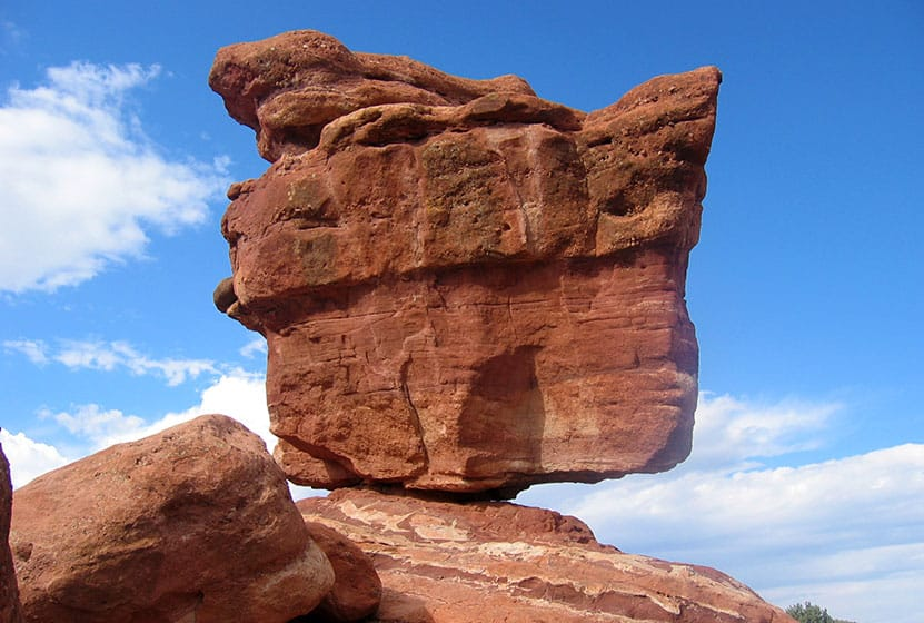 giant red rock balanced on rock fulcrum in garden of the gods