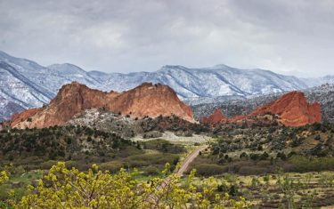 road leading into garden of the gods red rocks with snow dusted foothills and clouds in background