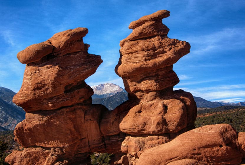 two red rock towers rock formation with pikes peak mountain in background