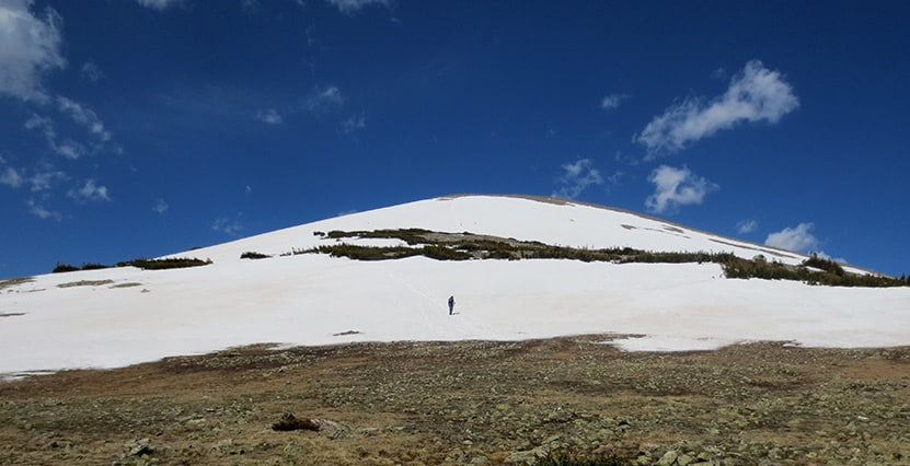 man hiking up snow covered st. vrain mountain in colorado