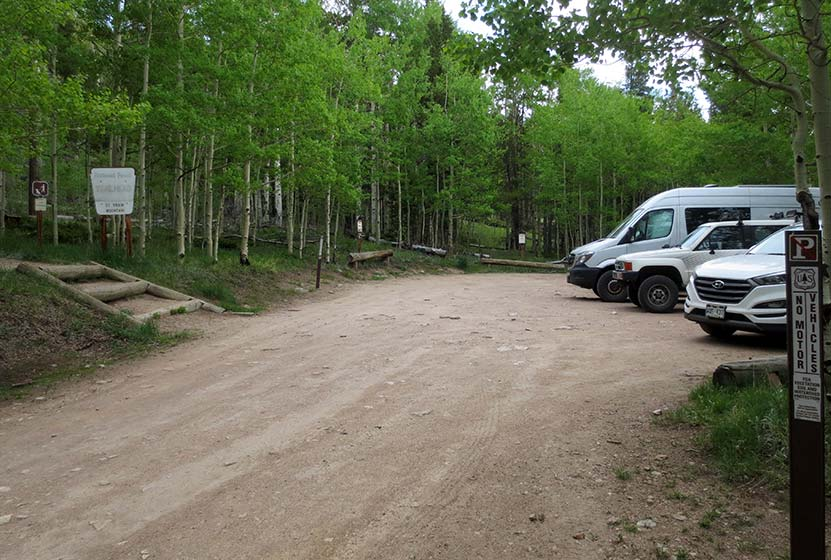 parking area at st. vrain mountain trailhead in colorado aspen trees and dirt road