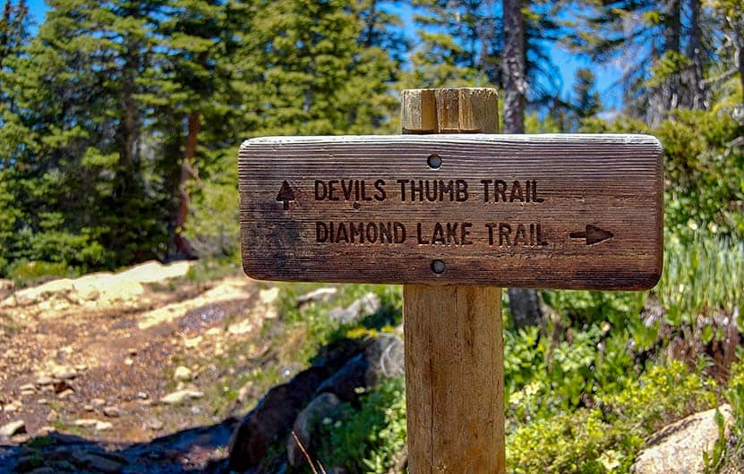wooden trail sign with evergreen trees and rock in background pointing direction to Devil's Thumb lake