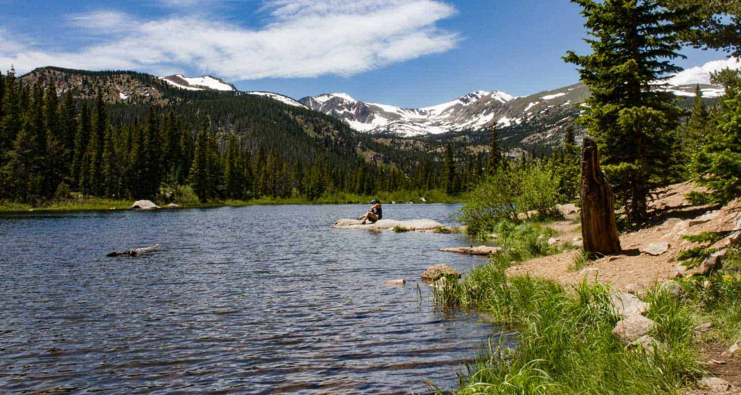 lost lake near nederland colorado with snow capped peaks and woman hiker