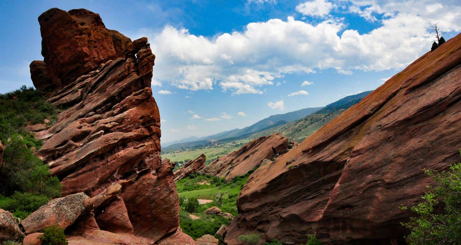 trading post trail at red rocks with green park below and blue skies with cumulus clouds at red rocks park near denver hike