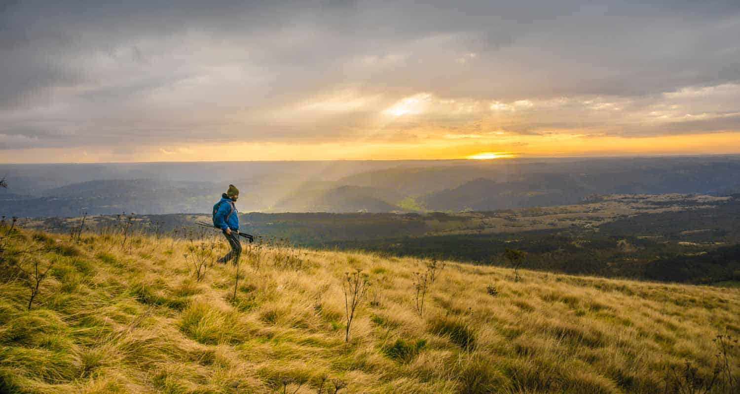 hiker at sunset on a grassy mountainside