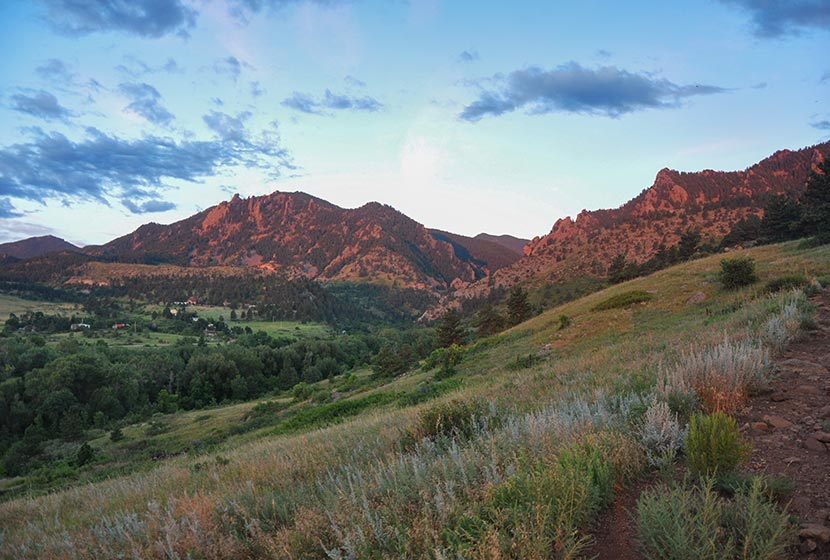 sunrise view from south mesa into eldorado canyon pink rock and green rolling meadows