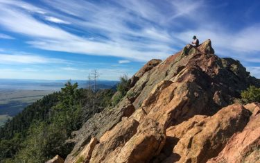 mountain peak with orange granite with hiker sitting on top against blue skies bear peak hike boulder colorado