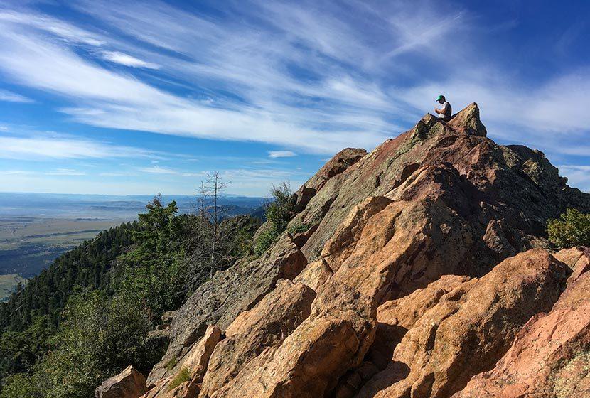 mountain peak with orange granite with hiker sitting on top against blue skies bear peak hike boulder colorado