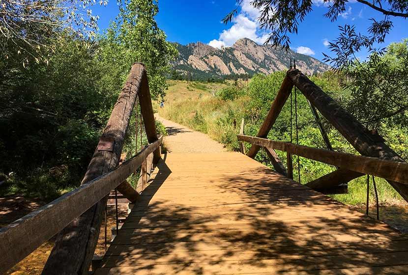 bridge across creek with bear peak and flatirons in distance trail for bear peak hike
