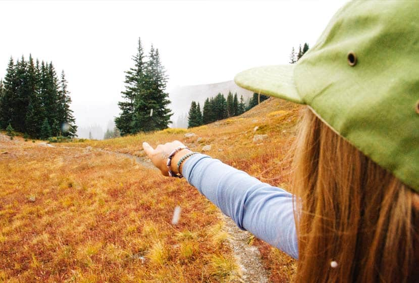 woman pointing down the trail toward evergreen trees with fog and snow falling easy beginner hikes near denver