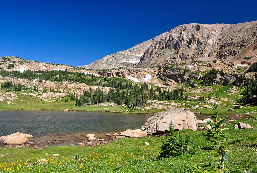 mountain with lion lake beneath it and blue skies on summer day rocky mountain national park in wild basin