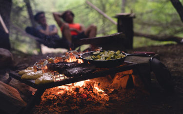 food cooking on grill above a hot fire with two people in background lounging in hammock camping meals