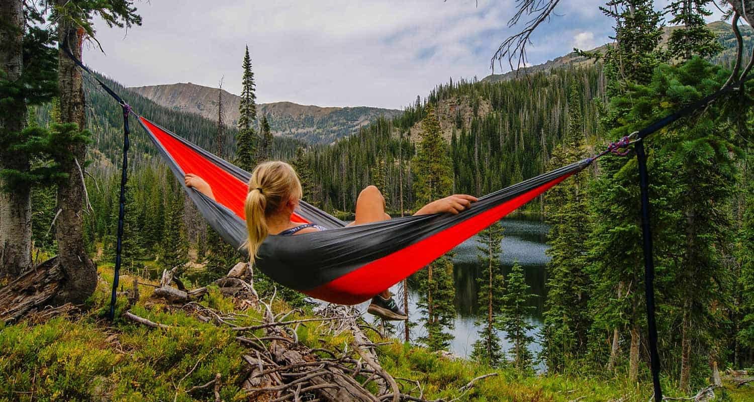 woman in hammock near high mountain lake with evergreen trees in foreground hikes by beauty near denver colorado