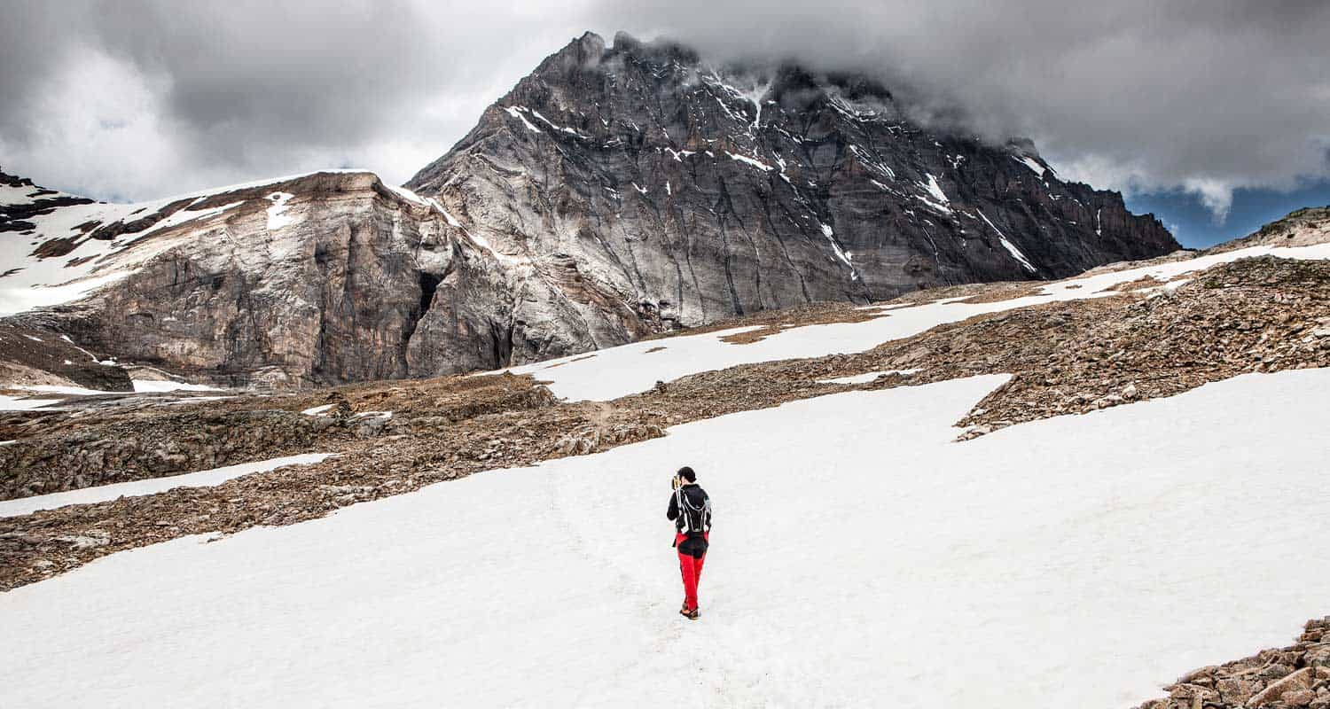 man hiking across snowfield with clouds and massif of mountain in front of him hikes by difficulty near denver