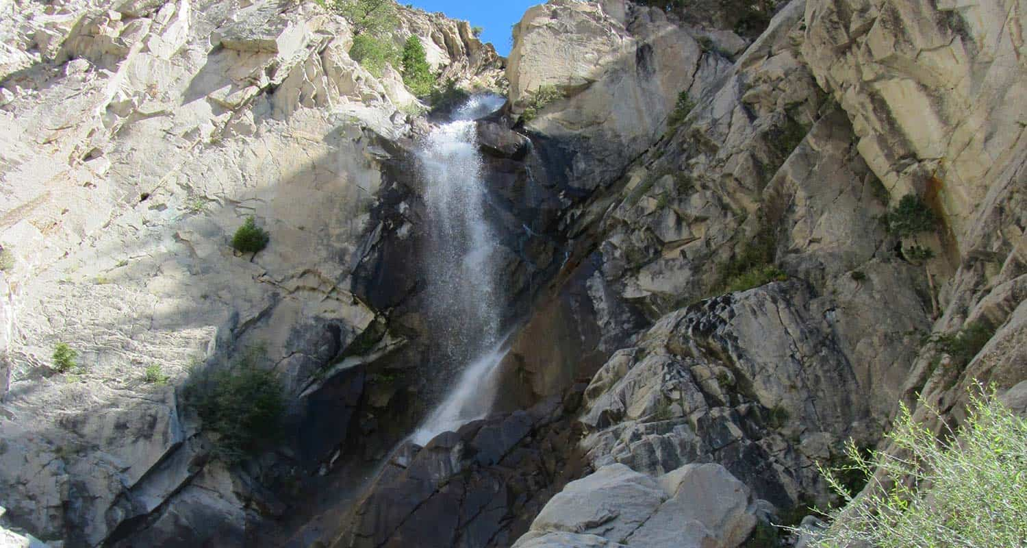 agnes vaille falls waterfall splashing over rock cliffs into creek below on hike near buena vista colorado