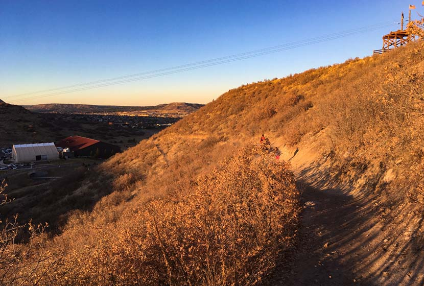 trail runners running loop trail at castle rock incllat sunset