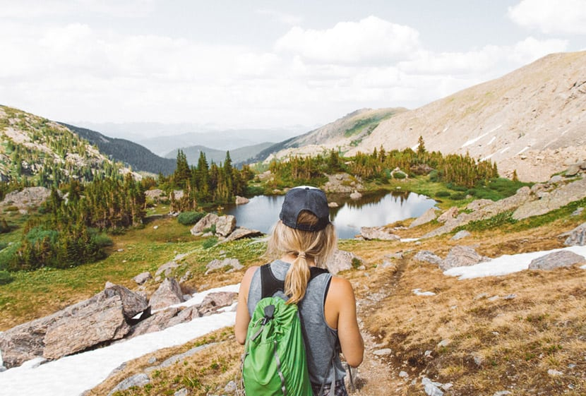 hiker in high country of colorado wearing hat with green backpack by colorado adventure photographer holly mandarich