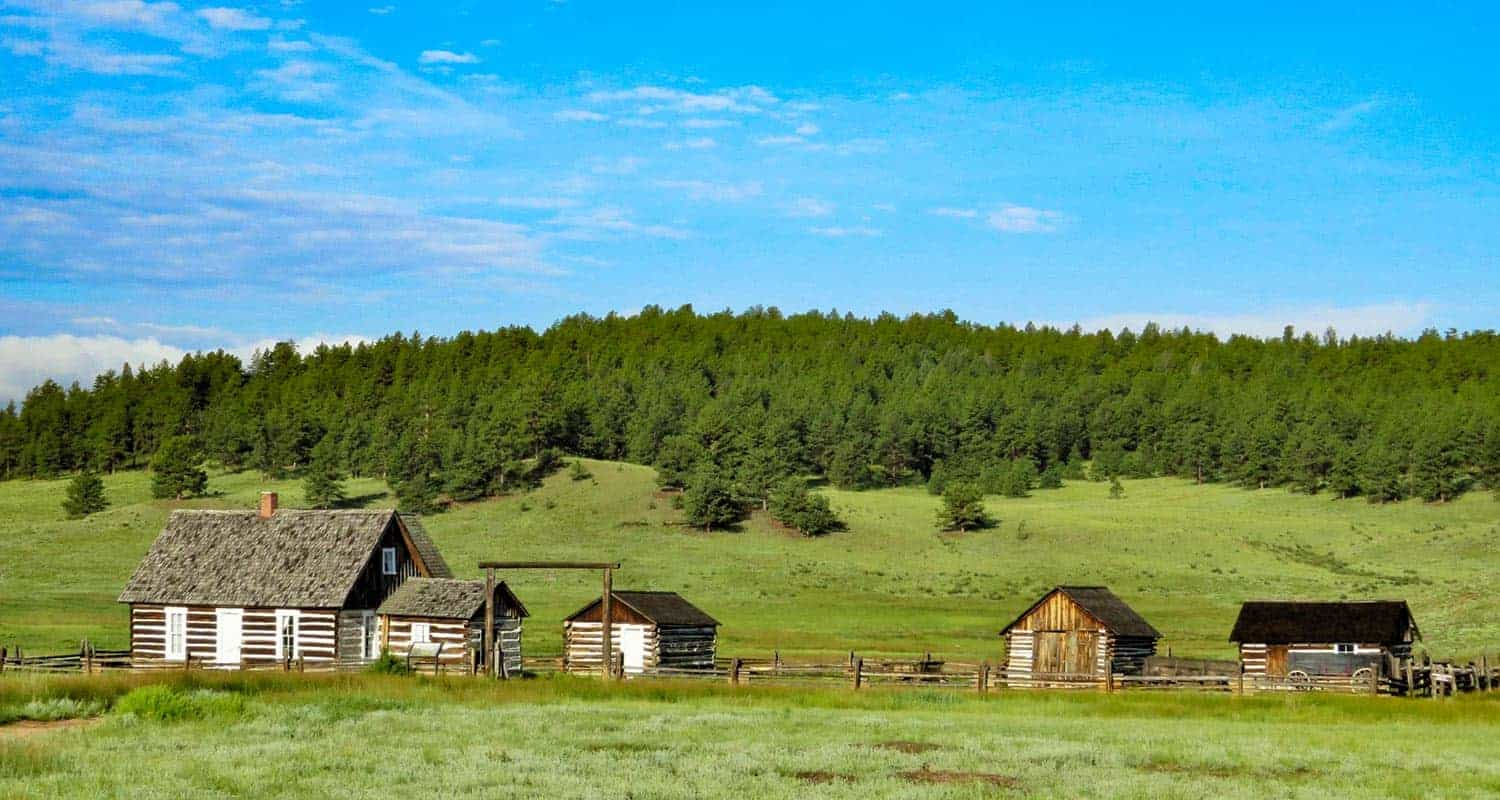 old cabin with barns in florissant colorado with green meadows hornbeck homestead at fossil beds national monument