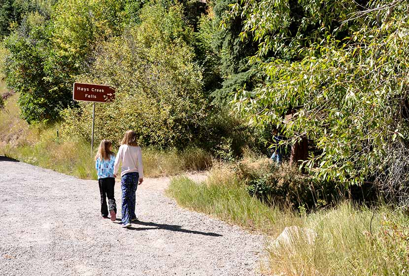 young hikers following sign to hays creek falls in colorado