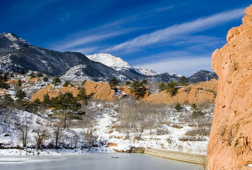 quarry pond in foreground and red rock formations on snowy afternoon with pikes peak in background on hike at red rock canyon open space in colorado springs