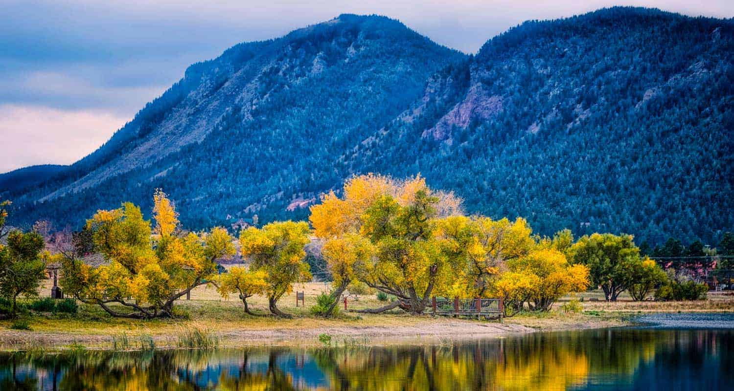 lakeshore at palmer lake in palmer lake colorado with willows and cottonwoods and frosted front range mountains in background along santa fe trail hike