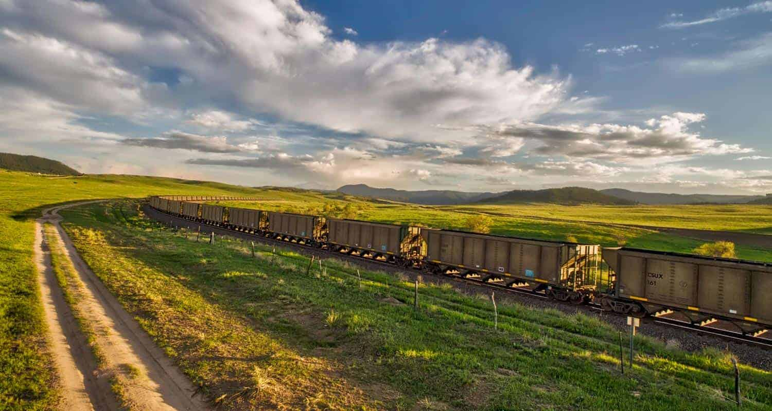 santa fe train running through green plains of greenland open space in colorado