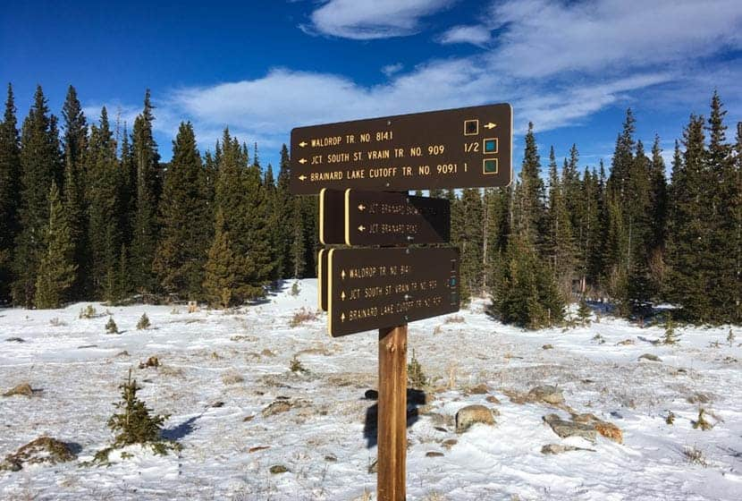 brainard lake waldrop trail signage with snow on ground and evergreen trees in background