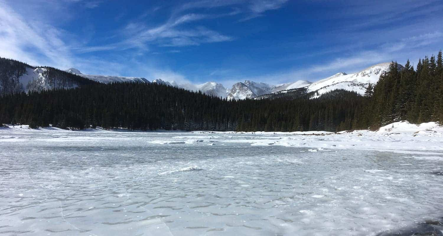 frozen brainard lake with snowcapped mountains in background on hike along waldrop trail to cmc cabin