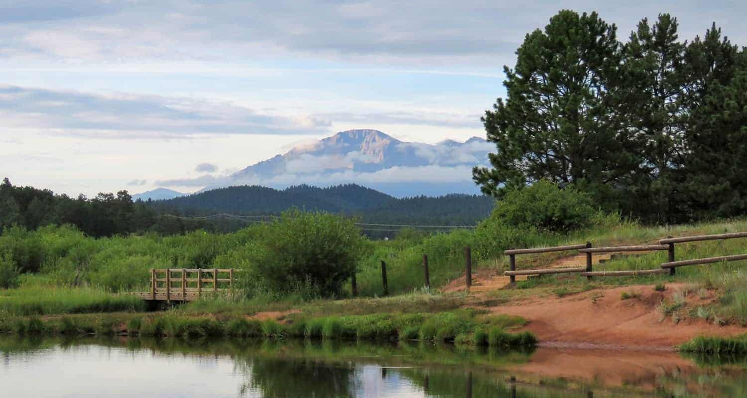 pikes peak in background with manitou lake in foreground near colorado springs
