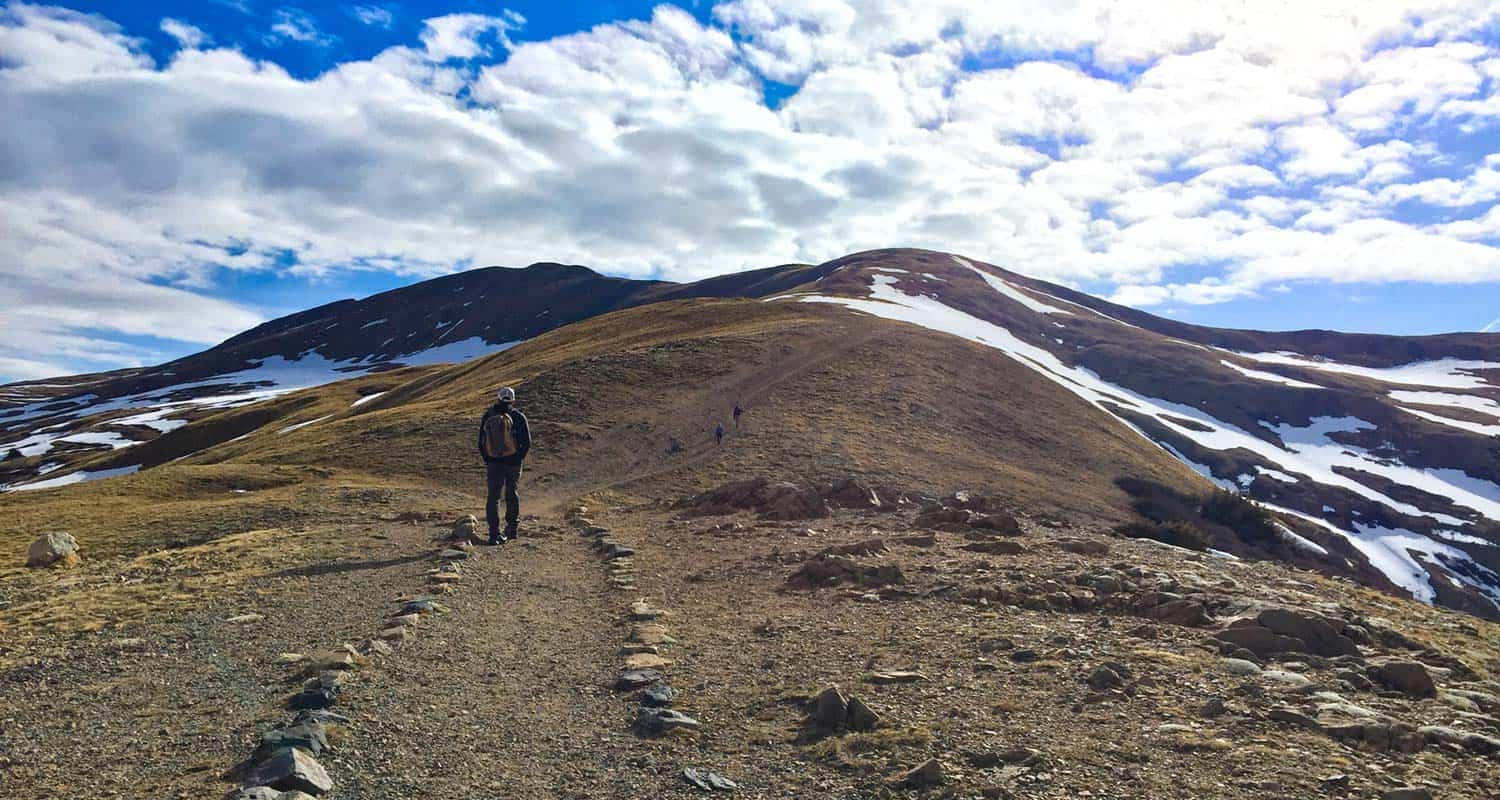 hiker at the beginning of the sniktau and grizzly trail on loveland pass with tundra of mountains in foreground and blue skies with clouds on hiike near denver