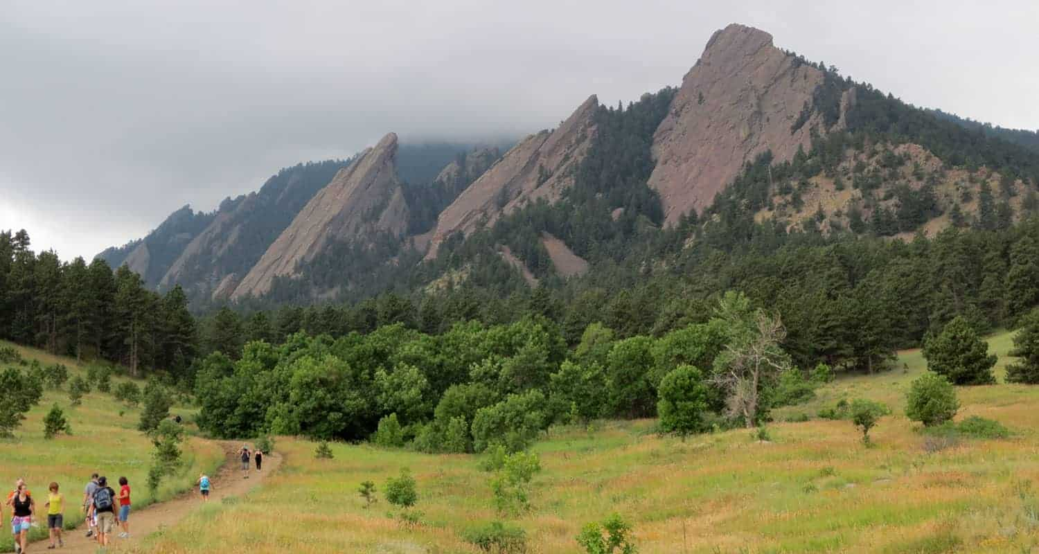 view of the flatirons in boulders chatauqua park with meadow in foreground and fog lifting